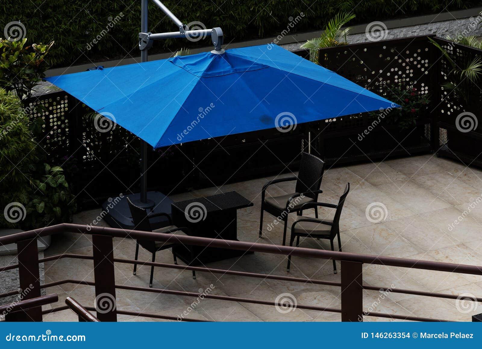 Plate-forme en bois avec les tables de billard ext?rieures avec la construction minimaliste de parapluies bleus