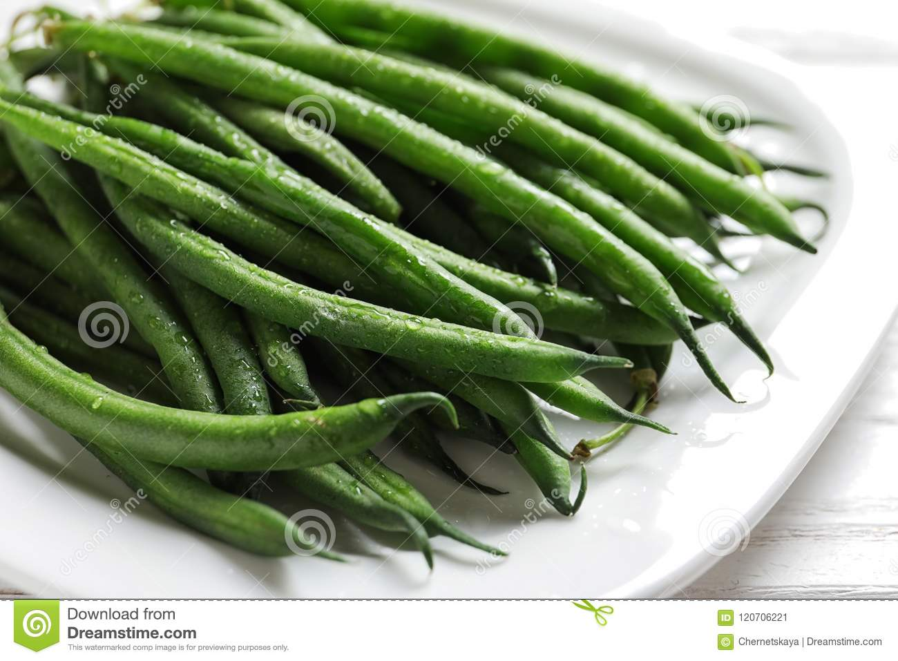Plate with fresh green French beans on table