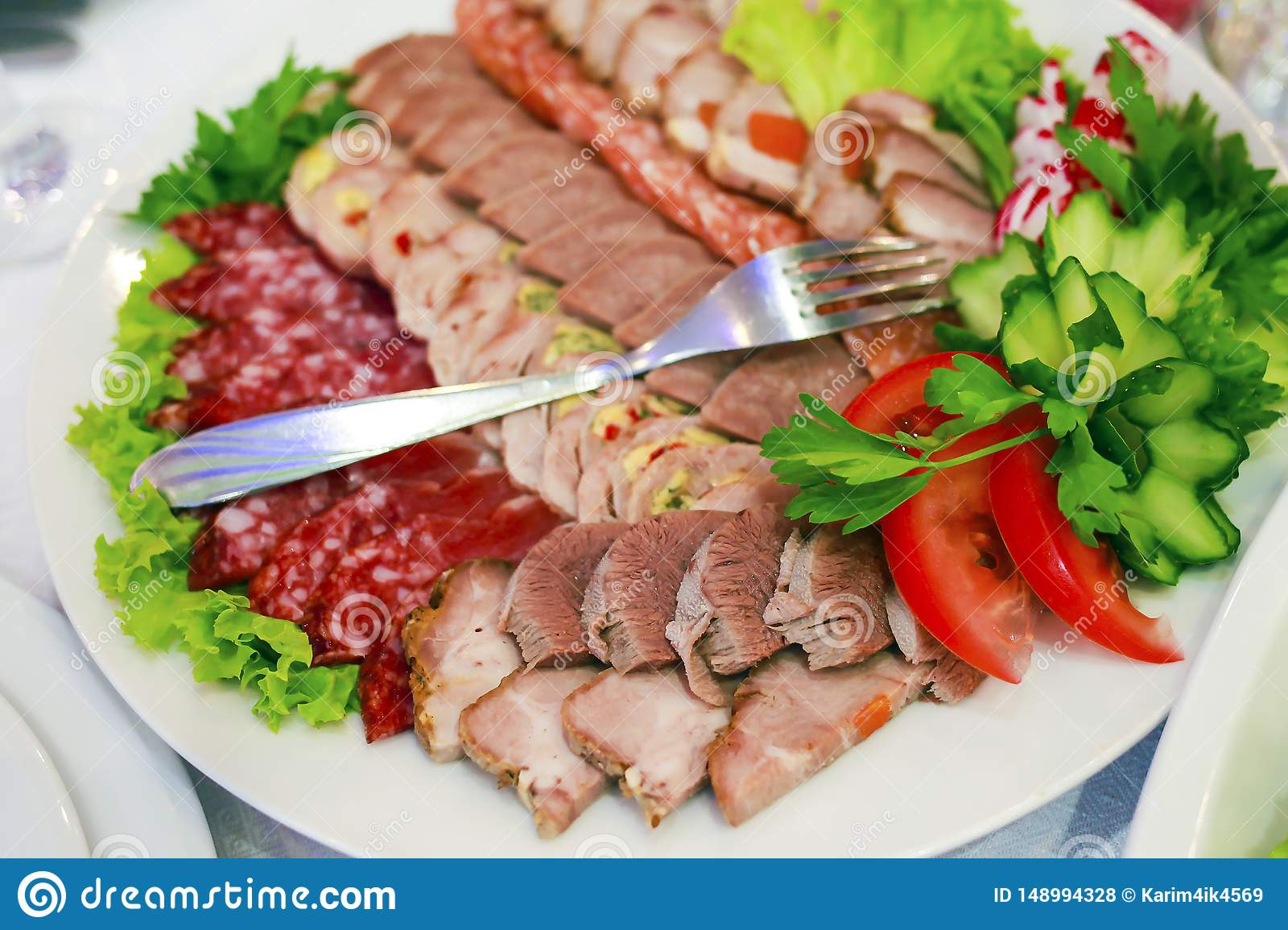A plate of ham, bacon, salami and sausages. Meat platter