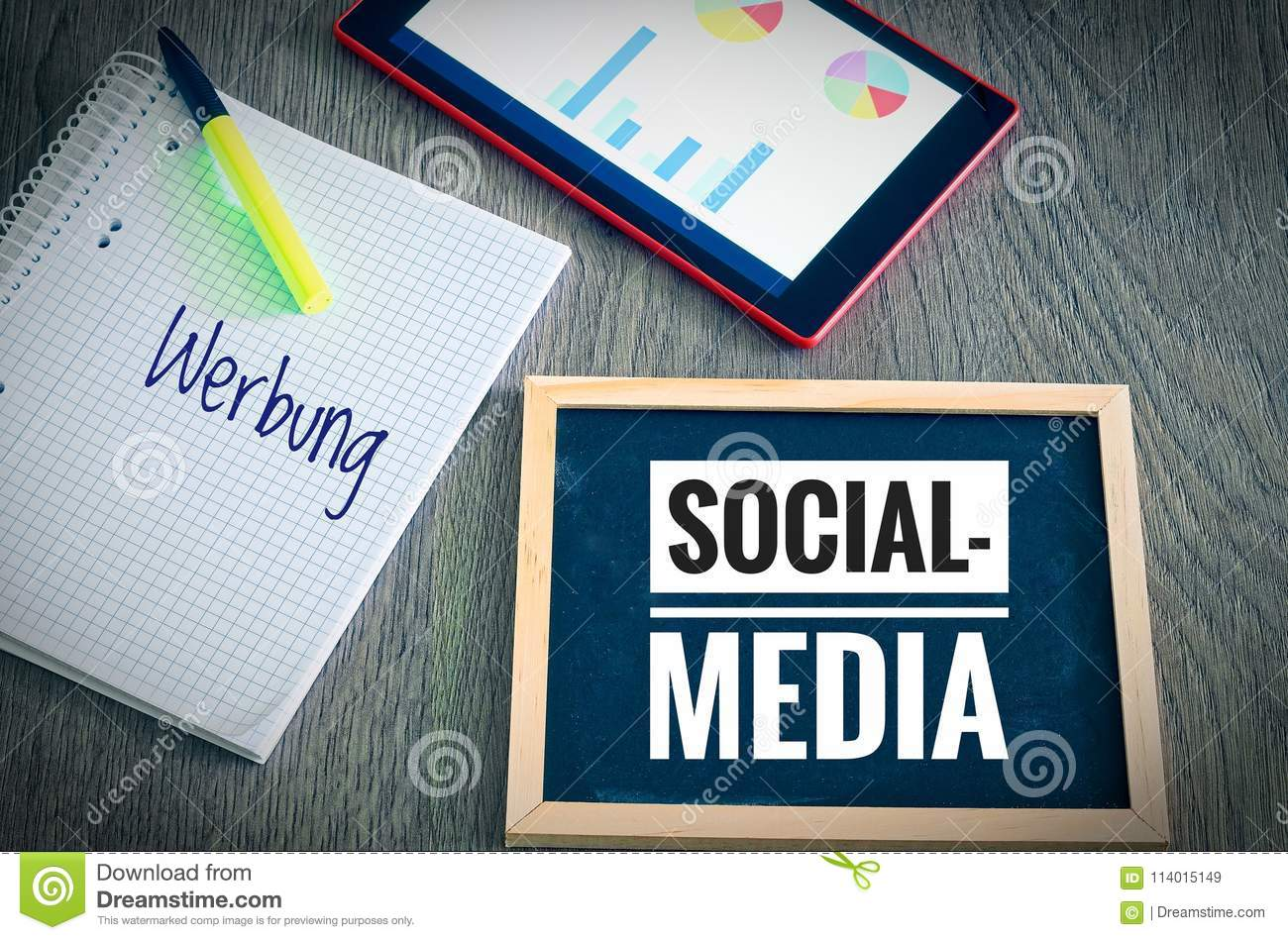Plate with the inscription Social Media and in german Werbung in english advertising with a tablet and blockto to symbolize the da