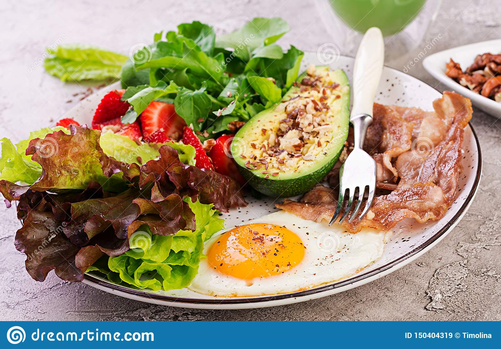 Plate with a keto diet food. Fried egg, bacon, avocado, arugula and strawberries.
