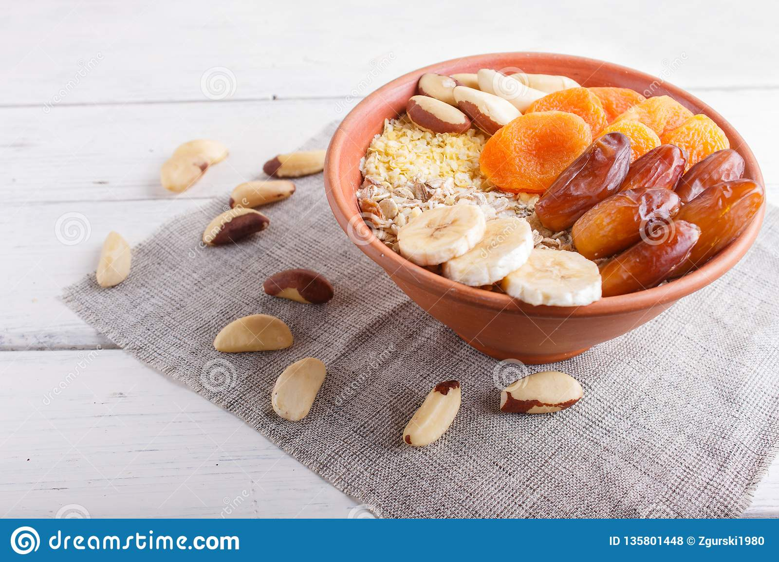 A plate with muesli, banana, dried apricots, dates, Brazil nuts on a white wooden background