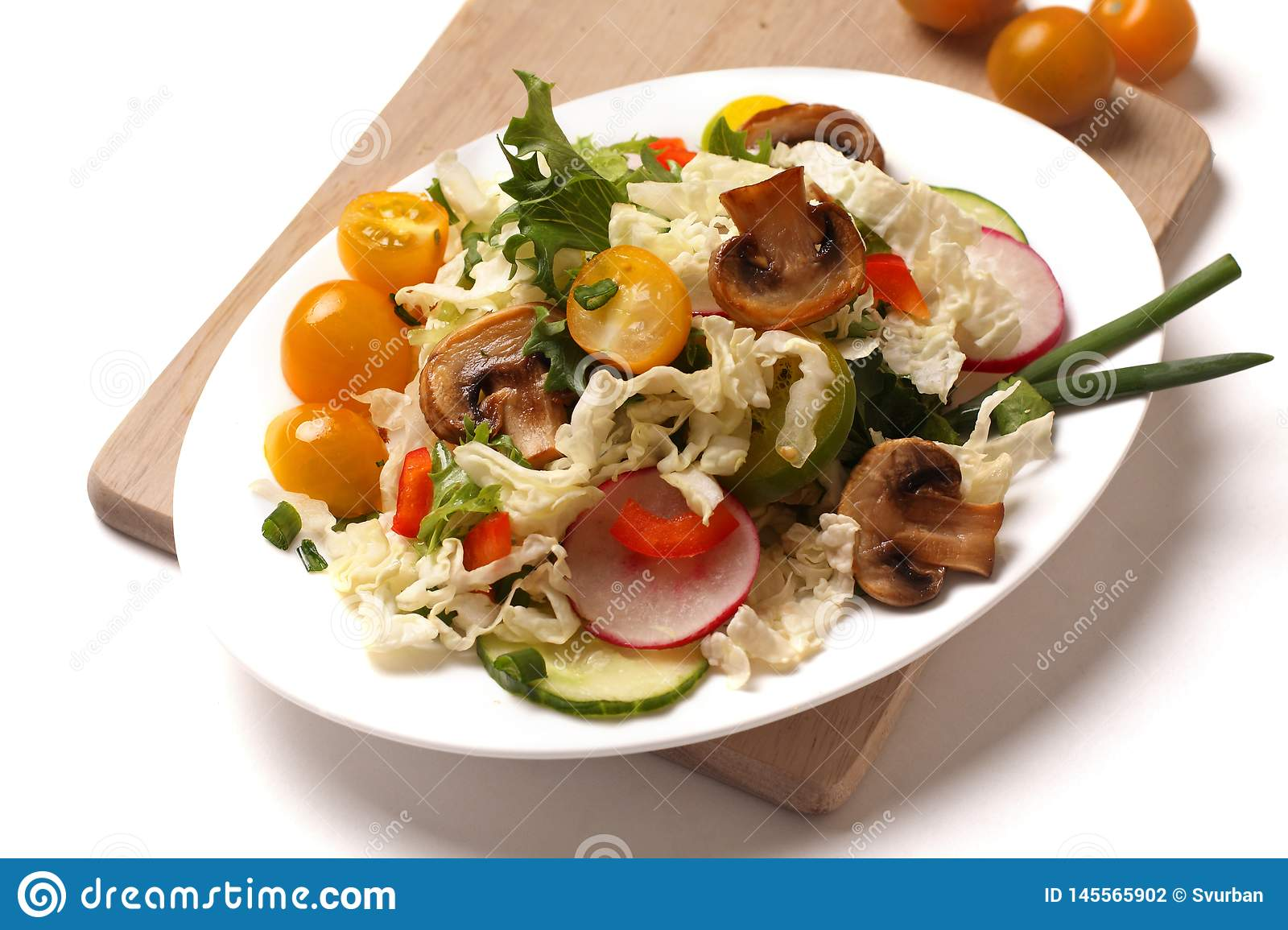 A plate of salad with vegetables, mushrooms and herbs