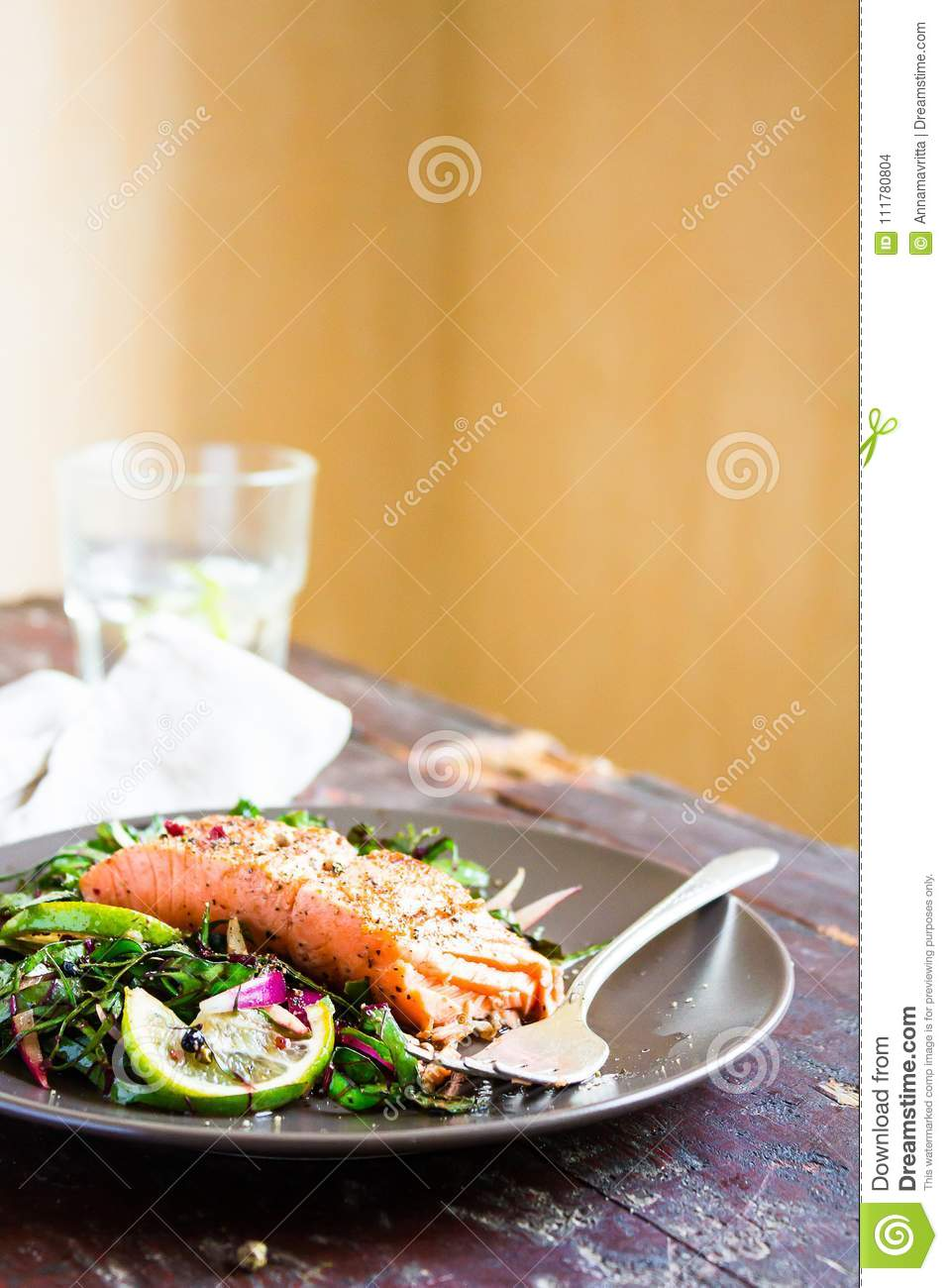 Plate of salmon fillet steak roasted with spices served with fresh salad with lime fruit and peppercorns on a wooden table, select