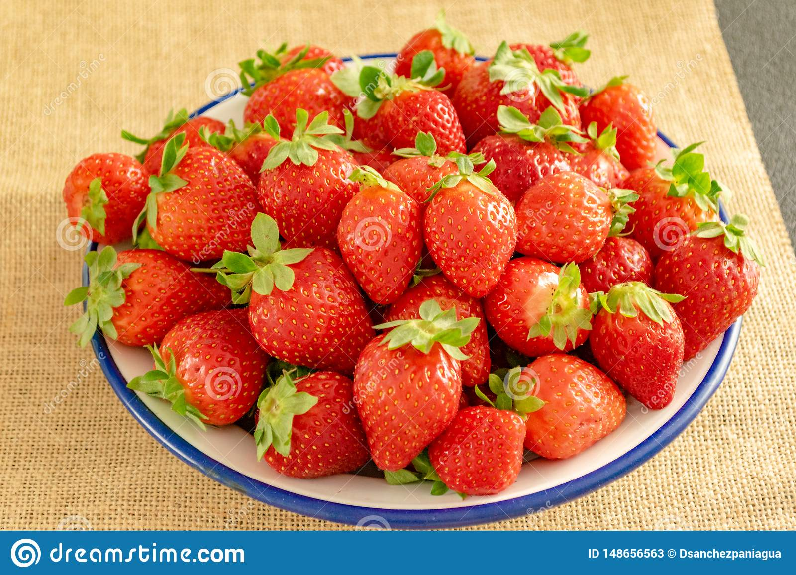 Plate of strawberries on textile background