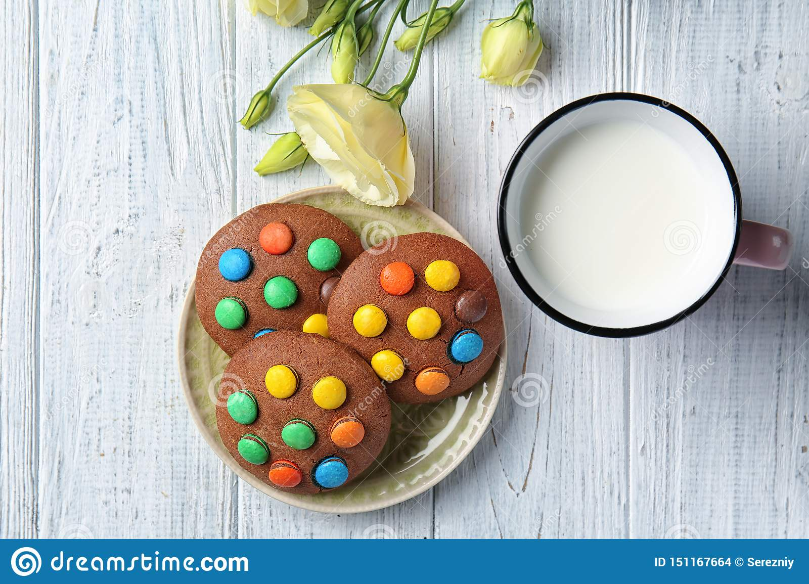Plate With Tasty Chocolate Cookies Mug Of Milk And Flowers On Wooden Table Stock Photo Image Of Flowers Pastry 151167664