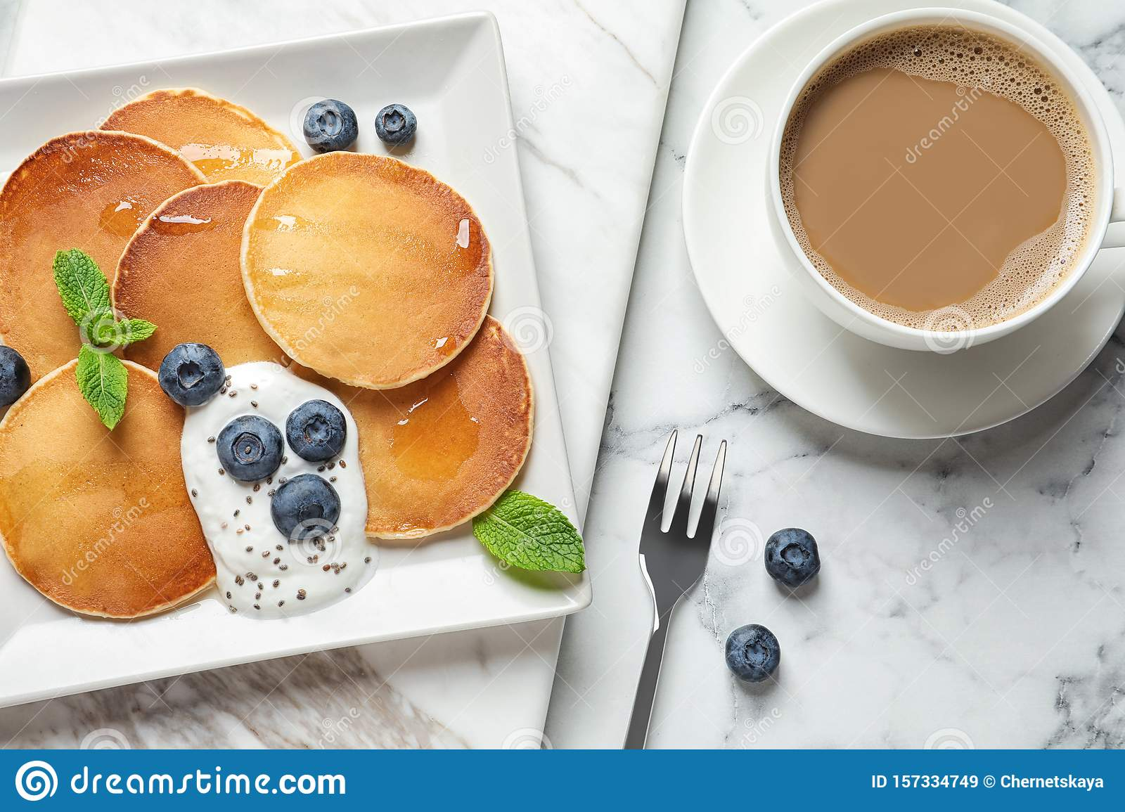 Plate of tasty pancakes with blueberries, sauce and mint on white marble table