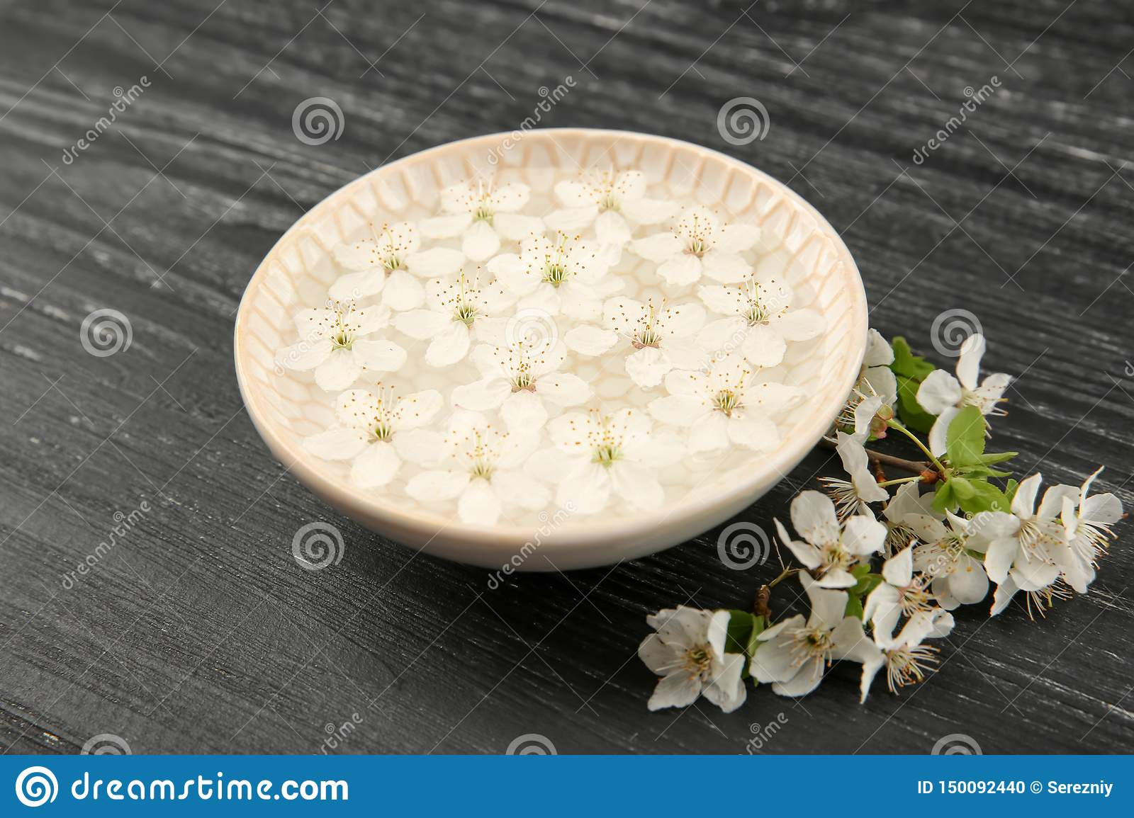 Plate with water and blooming flowers on dark wooden background