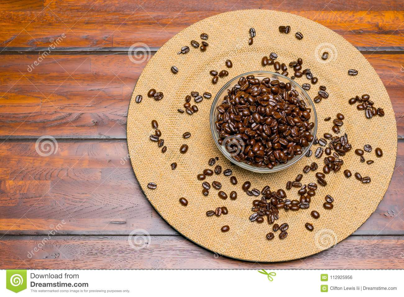 A plate of whole Coffee Beans on a wooden background.