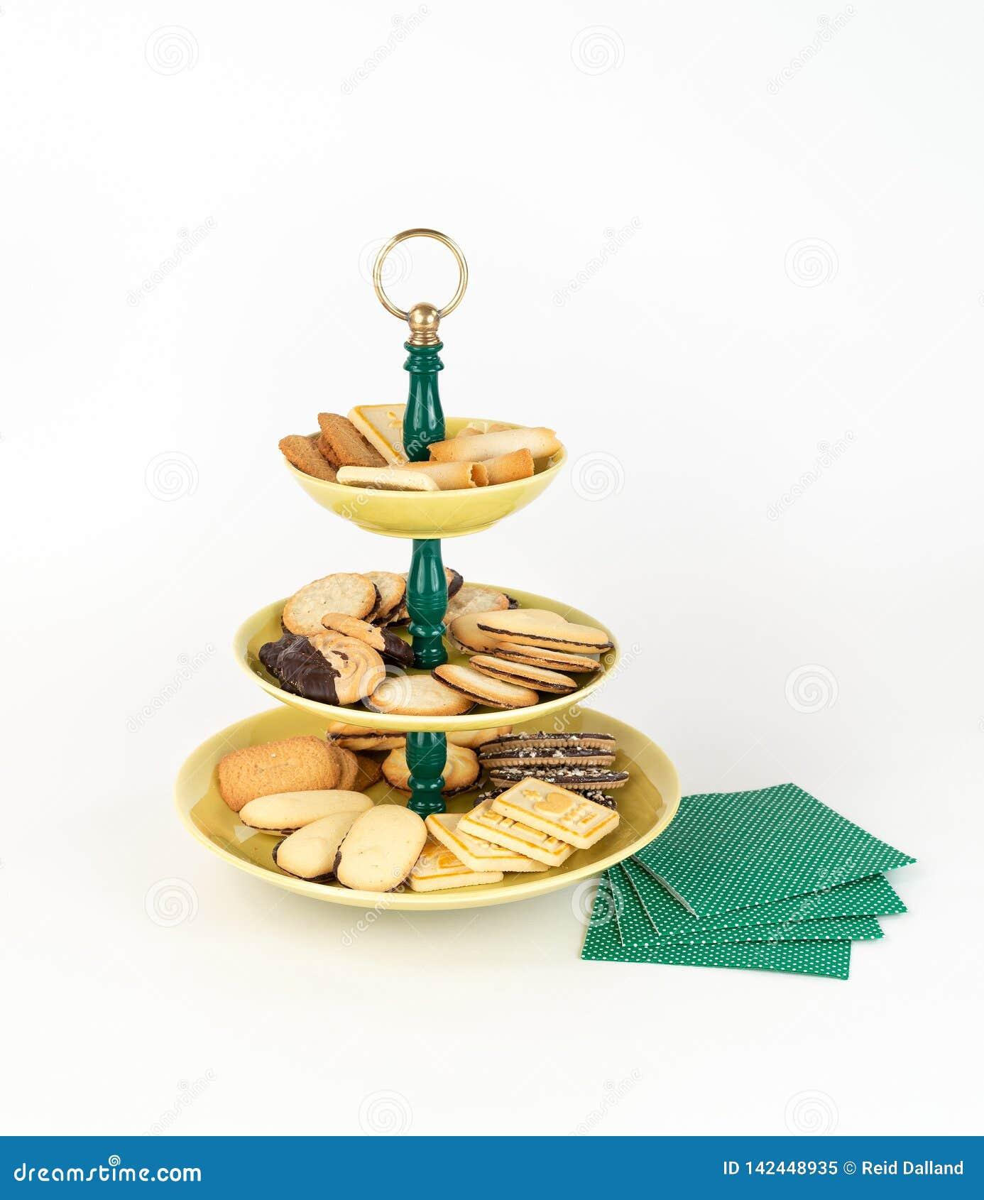 Plateau antique de serveur à trois niveaux avec un assortiment de biscuits et de serviettes