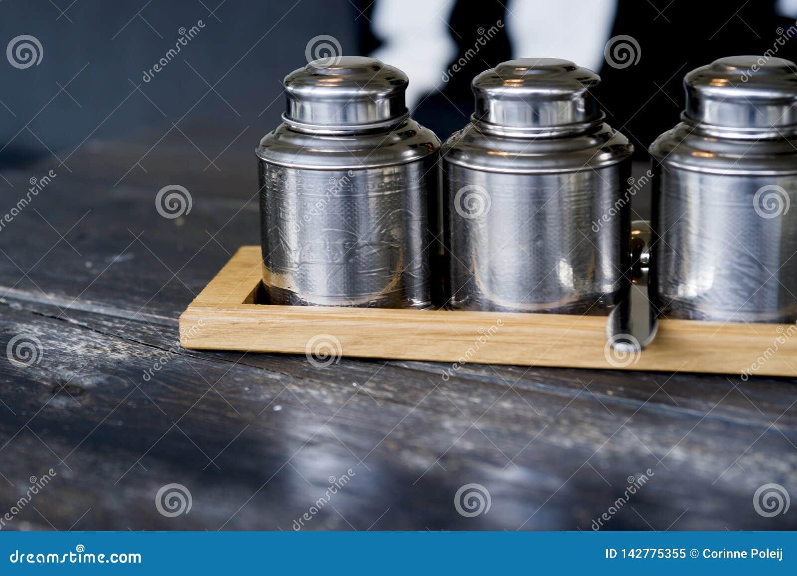 Plateau en bois avec des pots de thé en métal sur la table