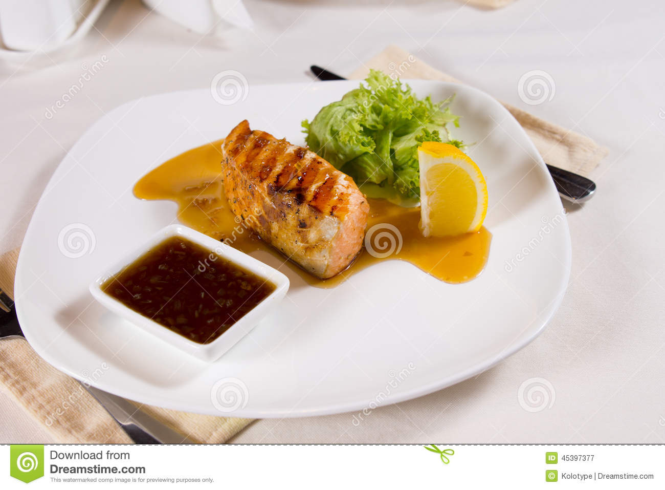 Plated Meal Of Grilled Fish With Garnishes Stock Photo