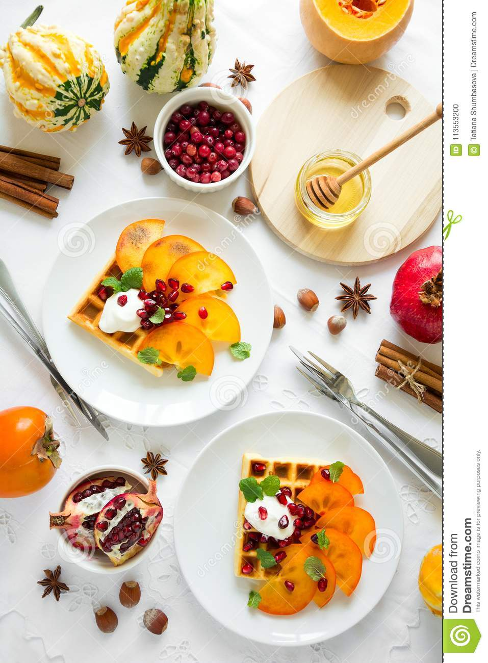 Plates of Belgian waffles with persimmon, pomegranate seeds and sour cream
