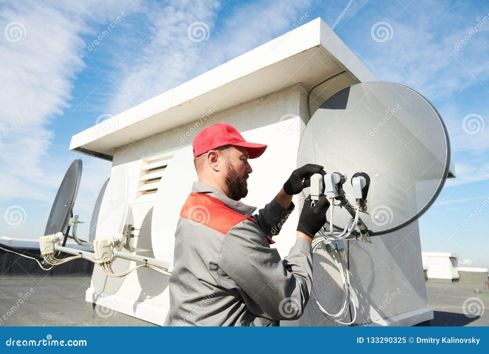 Plato de instalación y que cabe del trabajador del servicio de la antena de satélite para la televisión por cable