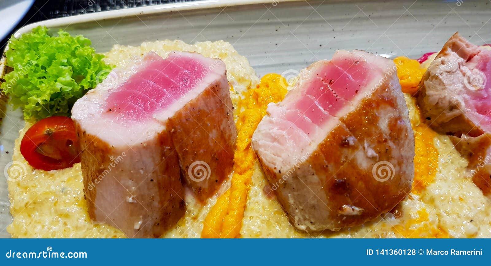 Plato de pescados: atún asado a la parrilla en una cama de patatas con los tomates y la ensalada