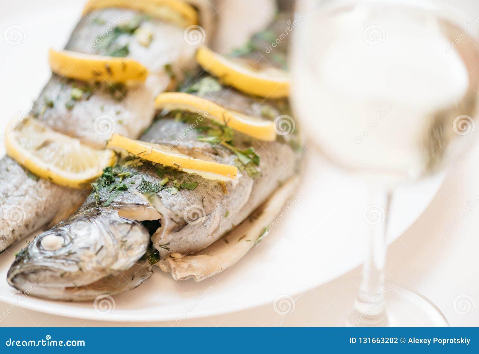 Plato de pescados en una placa blanca con el vidrio de vino blanco