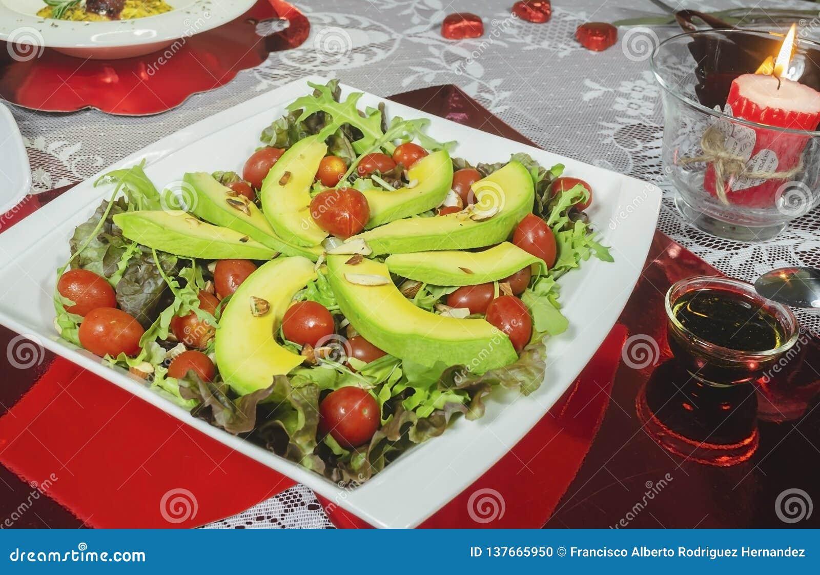 Plato del aguacate, tomates de cereza sanos, lechuga de la almendra y para la cena romántica