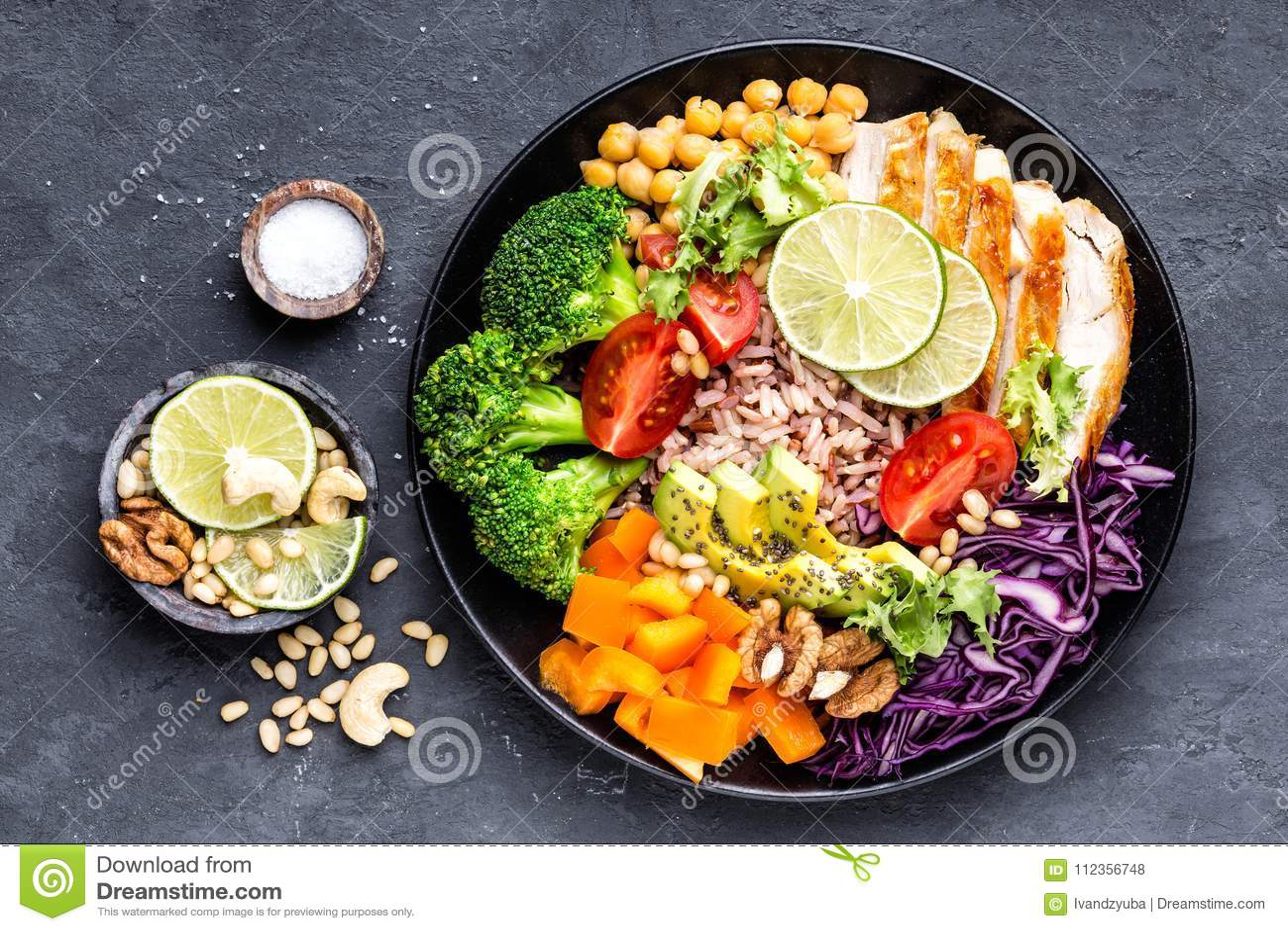 Plato del cuenco de Buda con el prendedero del pollo, arroz moreno, aguacate, pimienta, tomate, bróculi, col roja, garbanzo, ensa