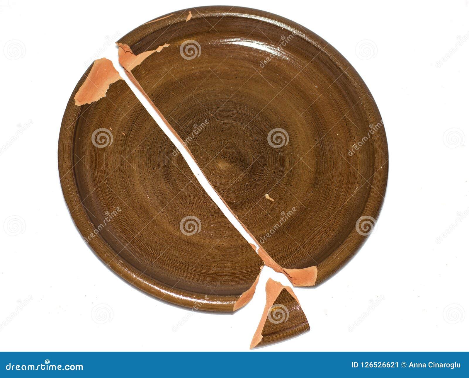 Plato quebrado de la arcilla Aislado en el fondo blanco