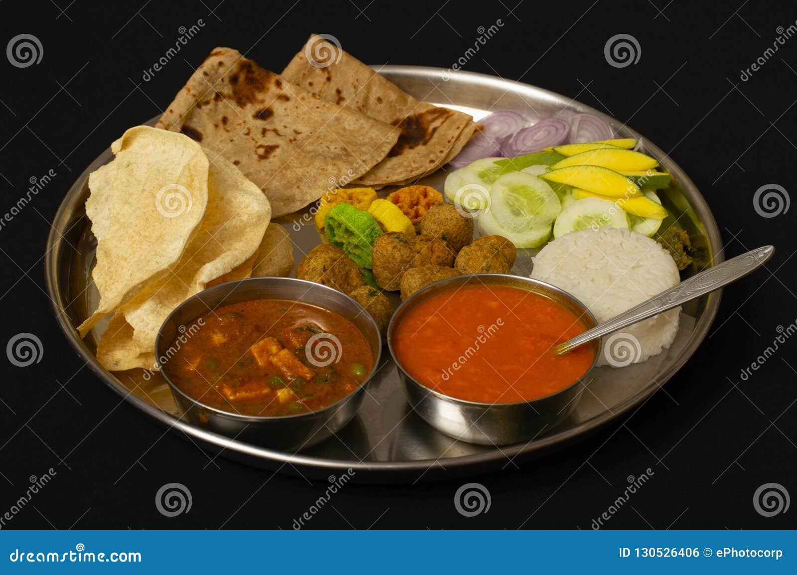 Plato típico del almuerzo de Maharashtrain con el chapati, jugo o aamras del mango, arroz, cebolla y verdura