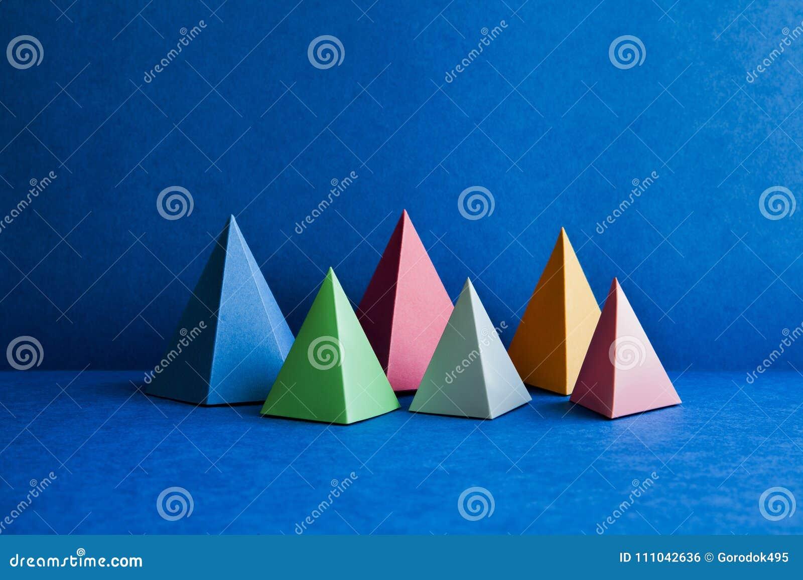 Platoniska fasta geometriska diagram Rektangulära objekt för tredimensionell pyramid på blå bakgrund Gula blåa rosa färger