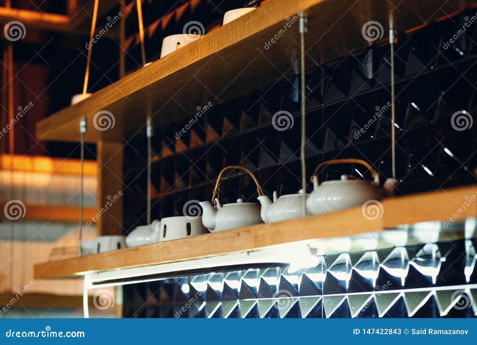Platos en los estantes en el restaurante en un fondo oscuro