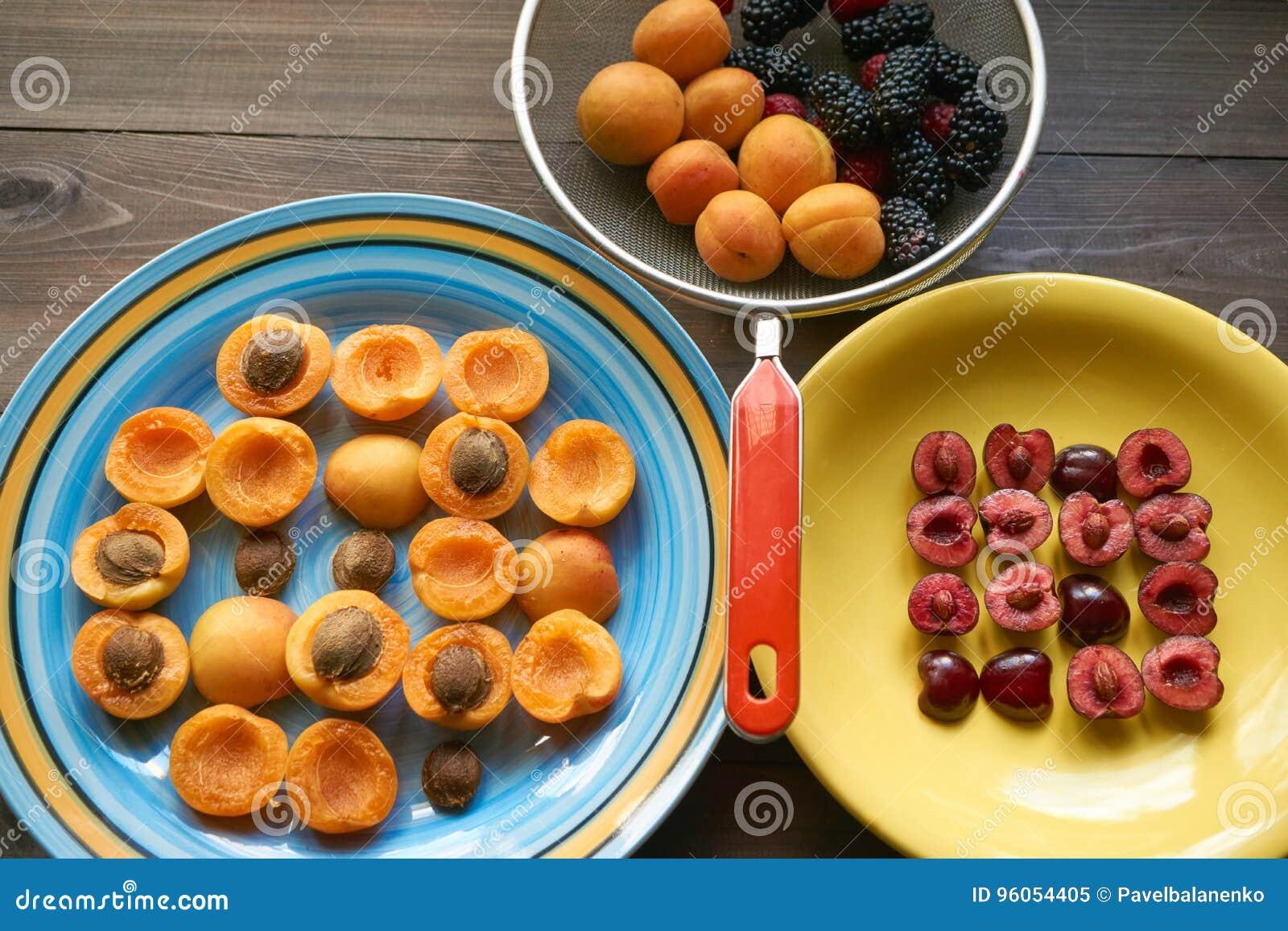 Plats avec des abricots et des cerises et passoire complètement des baies