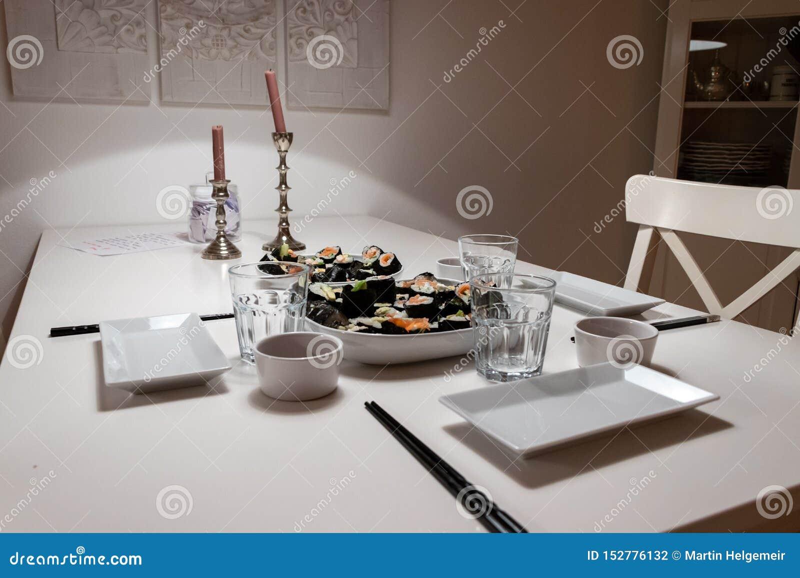 Plats et plats sur la table dans un appartement l individu a fait le petit pain de sushi Dîner romantique avec la lumière ambiant