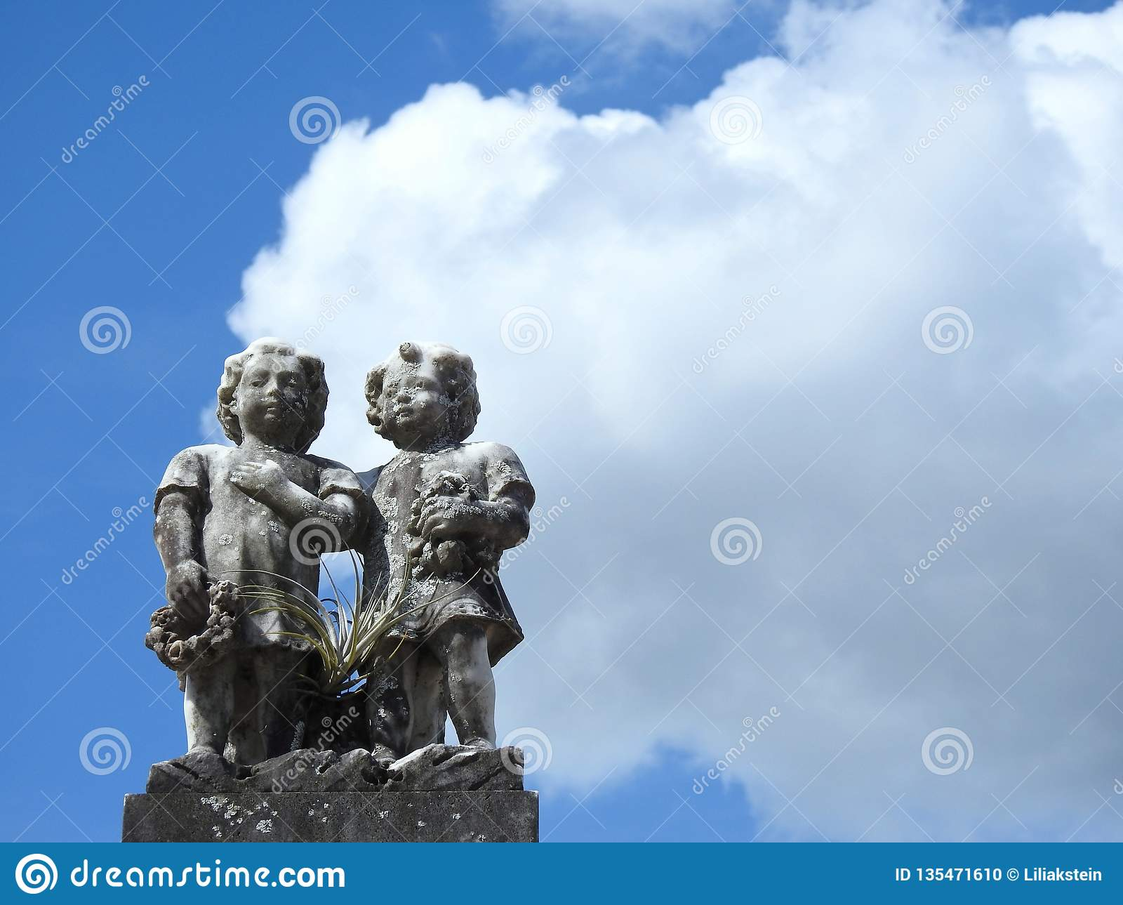 Plats i en kyrkogård: gammal stenstaty av två barn mot en himmel med stora moln på en solig dag