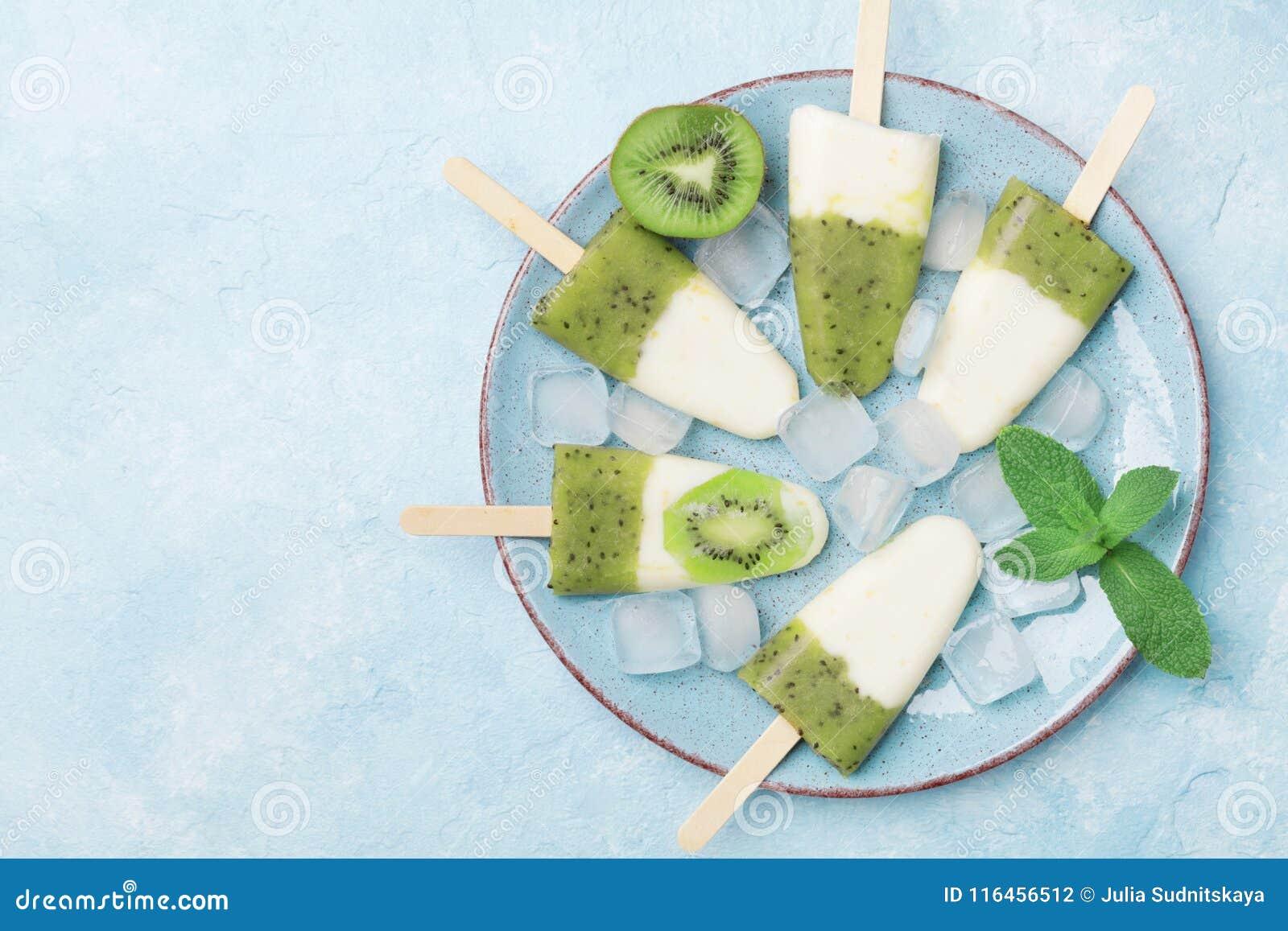 Platta av hemlagad frukt- glass eller isglassar från bästa sikt för för kiwismoothie och yoghurt Uppfriskande sötsaker för sommar