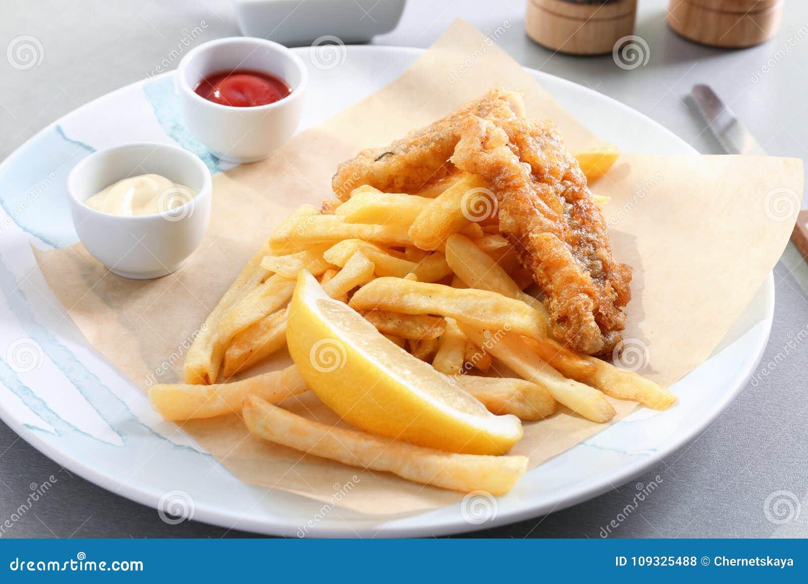 Platta med den smakliga stekte fisken, chiper och såser på tabellen