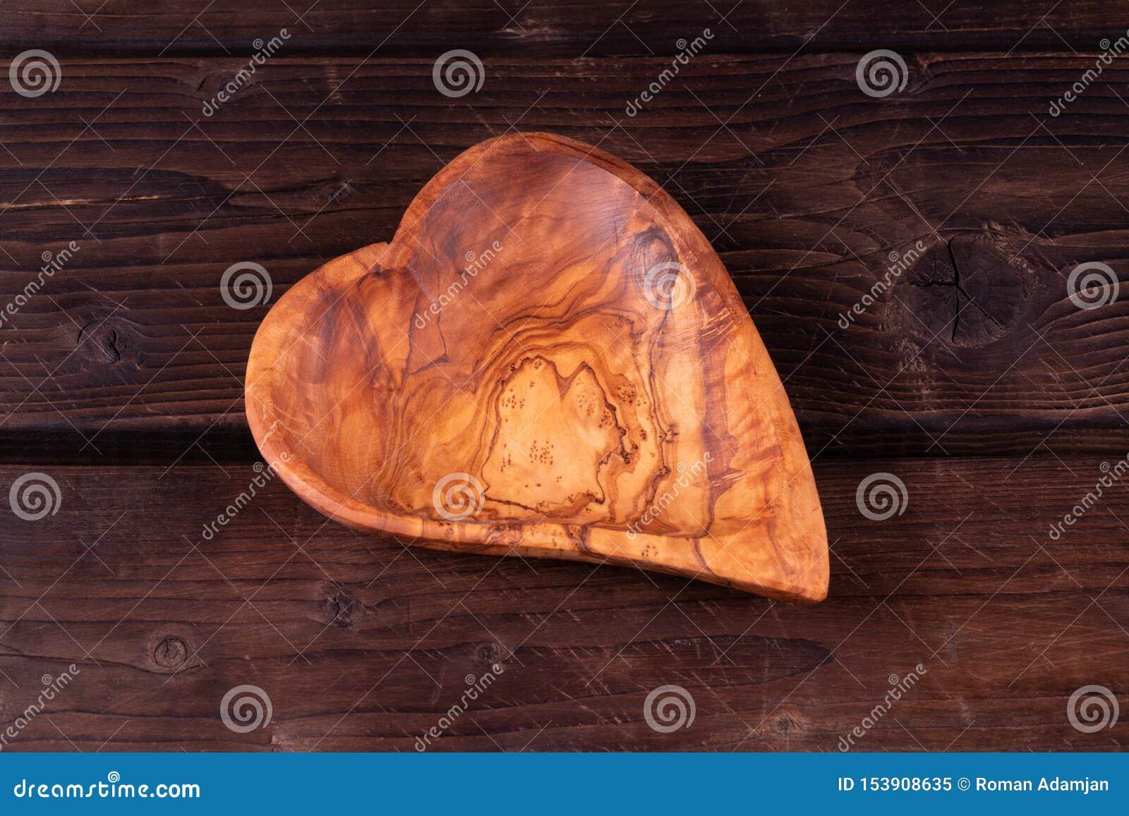 Plattahjärtaform på en träbakgrund, den låga tangenten, hand - gjorde, lantligt