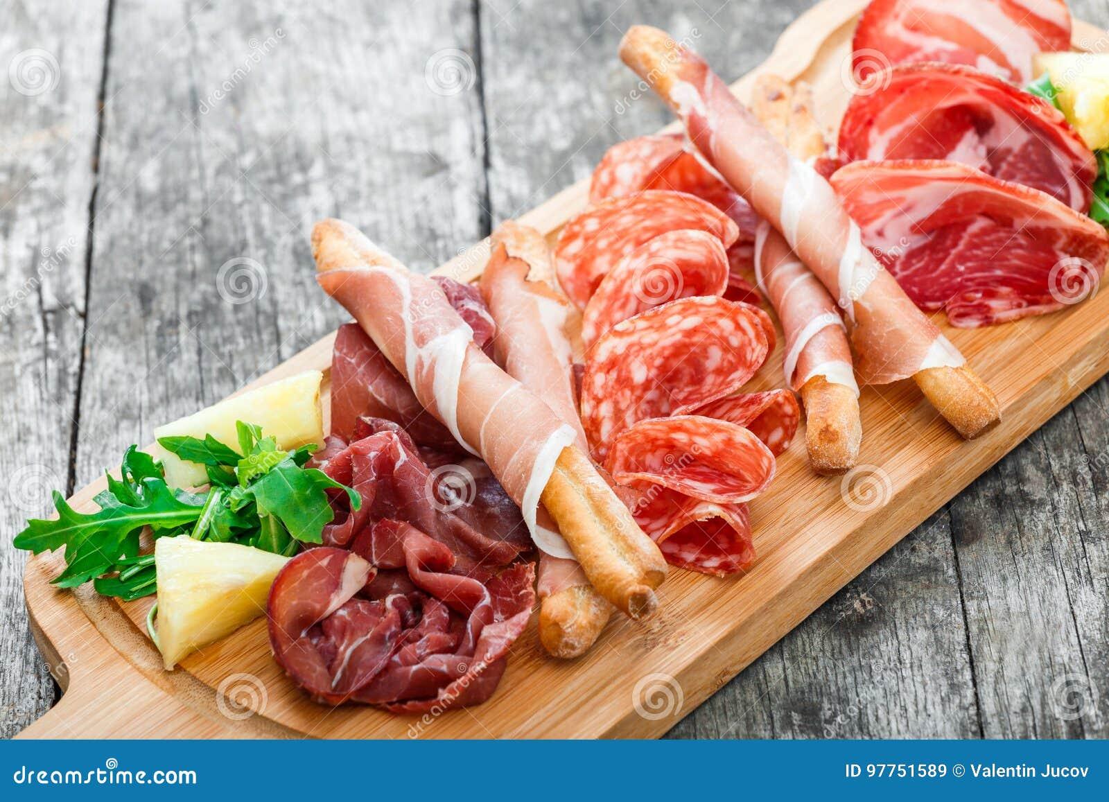 Platte des kalten Fleisches der Antipastoservierplatte mit grissini Brotstöcken, Prosciutto, Scheiben Schinken, Trockenfleisch vo
