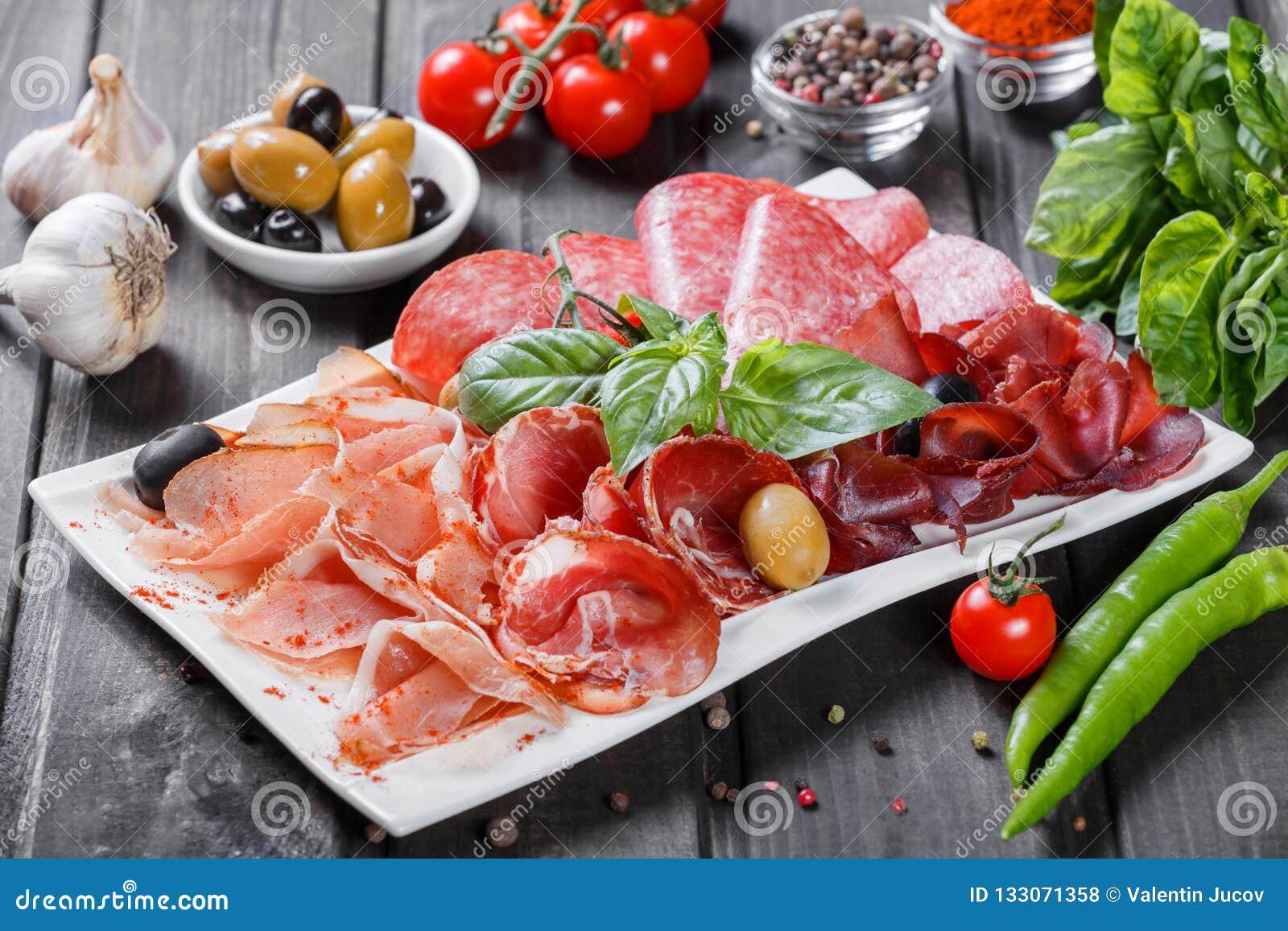 Platte des kalten Fleisches der Antipastoservierplatte mit Prosciutto, Scheiben Schinken, Salami, verziert mit Basilikum und Oliv