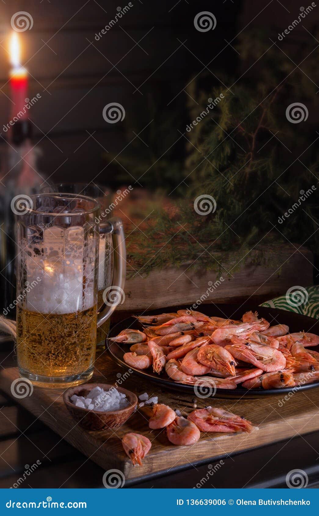 Platte ist von der Garnele voll Nahe einem Glas Bier Schimmerndes mysteriöses Licht
