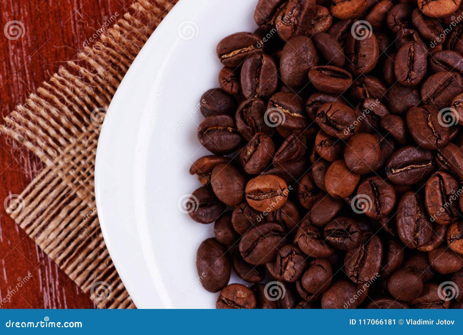 Platte mit mit Kaffeebohnen eine Spitzen-cpncept Ansicht