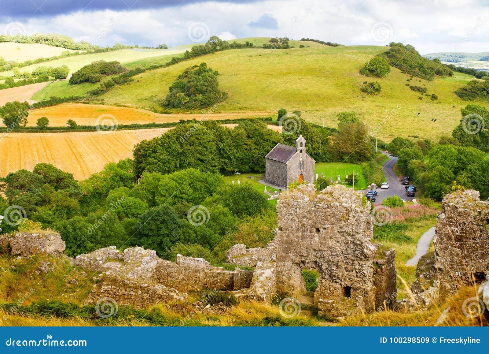 Plattelandslandschap met geruïneerde kasteel, heuvels, bos, weiden en hemel