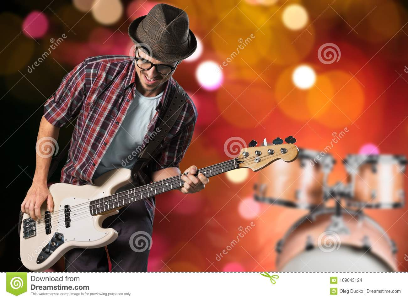 Male Guitarist playing music on blurred background
