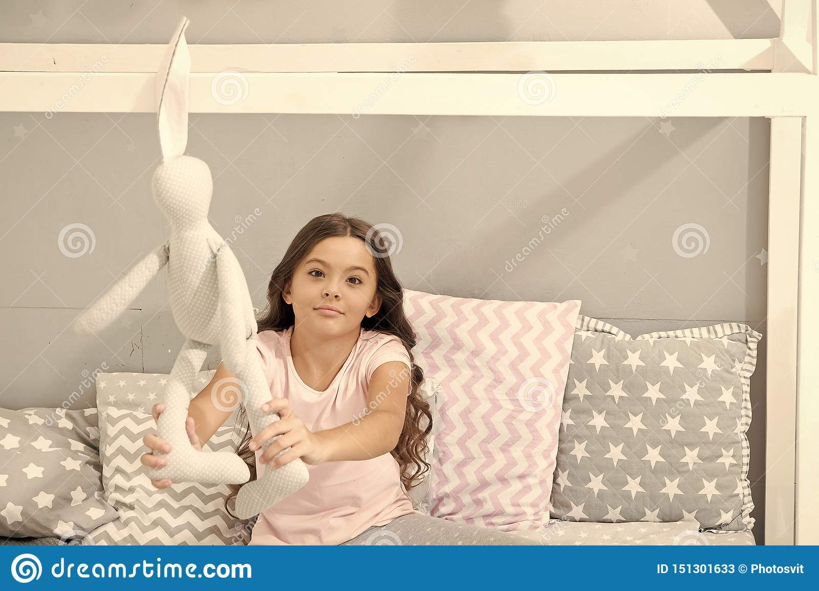 Play soft toy before go sleep. Girl long curly hair enjoy evening time with favorite toy. Kid sit bed and play bunny toy
