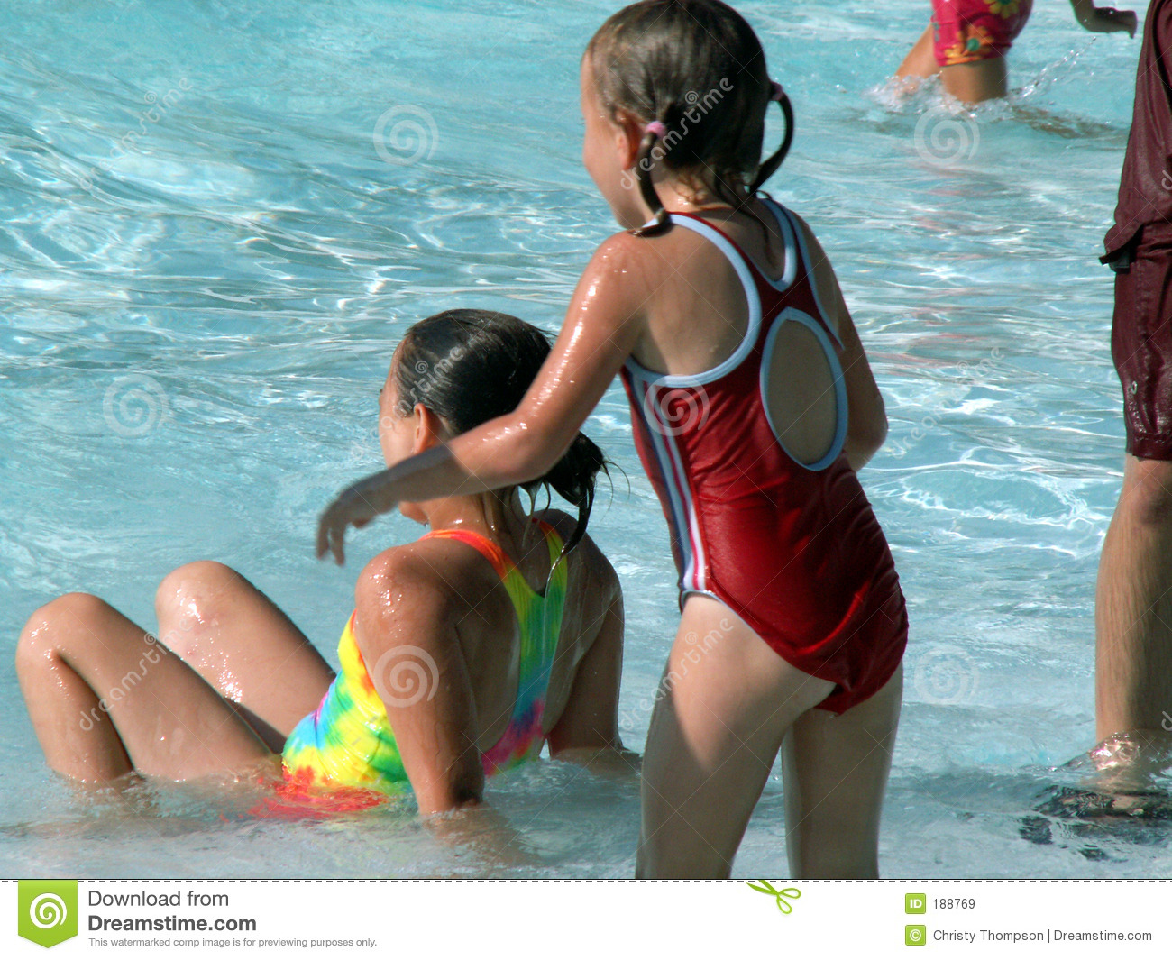 Two girls in swimming pool. focus on girl sitting down.