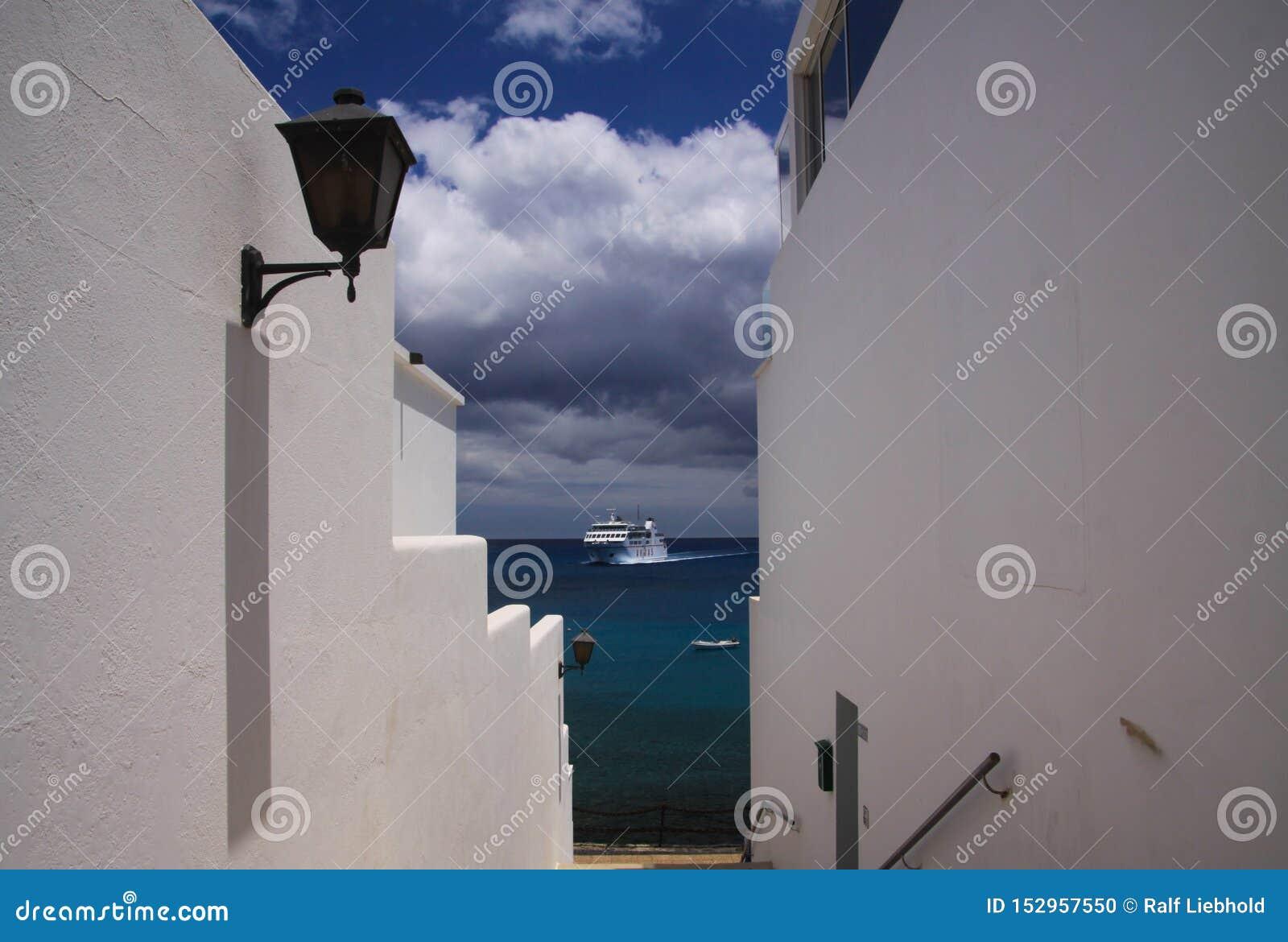PLAYA-BLANCA, LANZAROTE - JUNI 14 2019: Sikt längs vita väggar av huset på färjan som ankommer från Fuerteventura