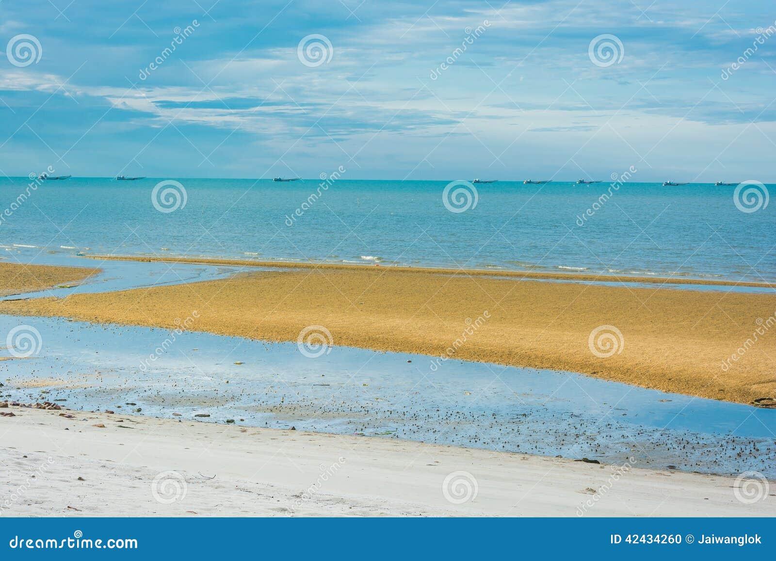 Playa con los barcos de pesca en el mar