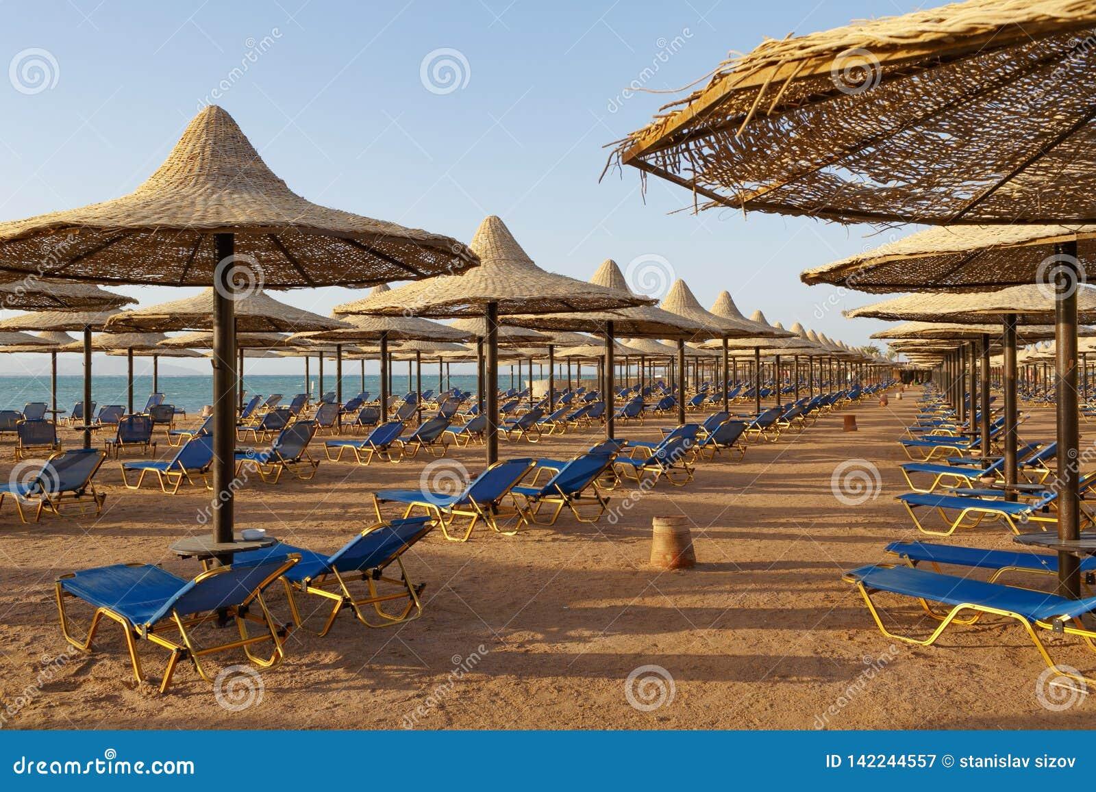 Playa con los sunbeds debajo de los parasoles de playa de la paja en la costa