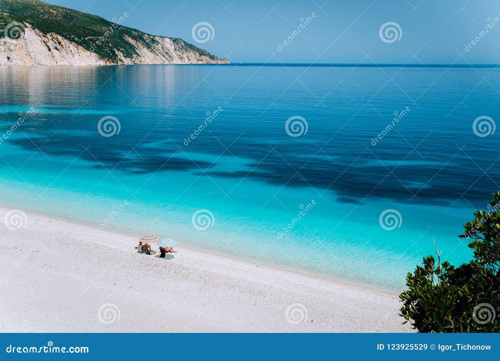 Playa de Fteri, Kefalonia, Grecia Los pares turísticos irreconocibles solos que ocultan de frialdad del paraguas de sol se relaja