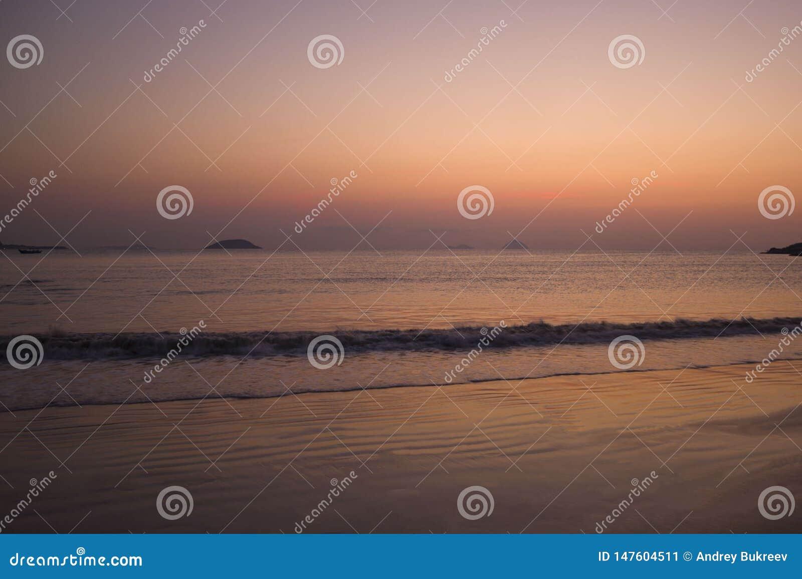 Playa del mar en la salida del sol y la puesta del sol