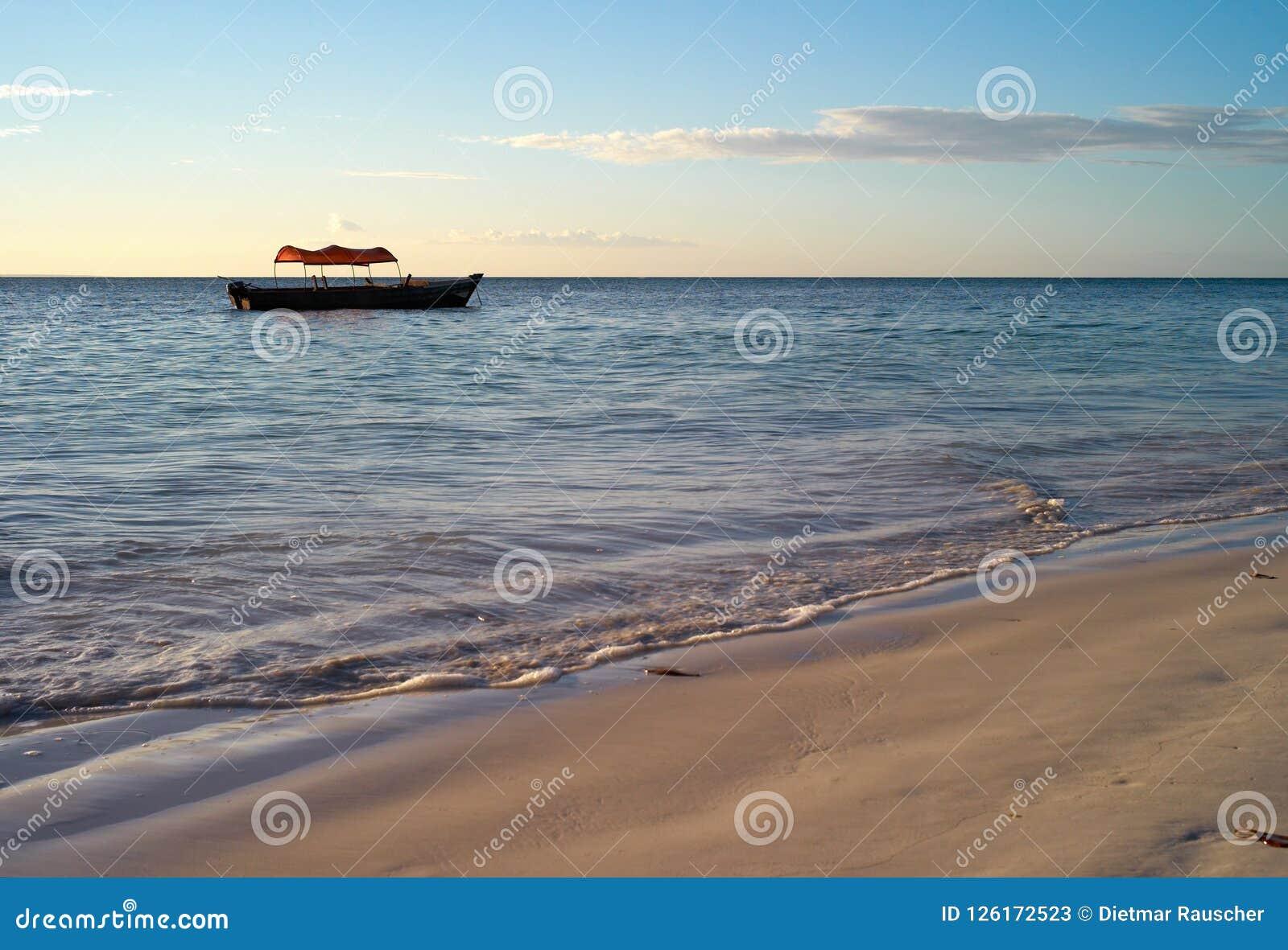 Playa hermosa con el pequeño barco de pesca en la playa de Michamvi, Zanzíbar