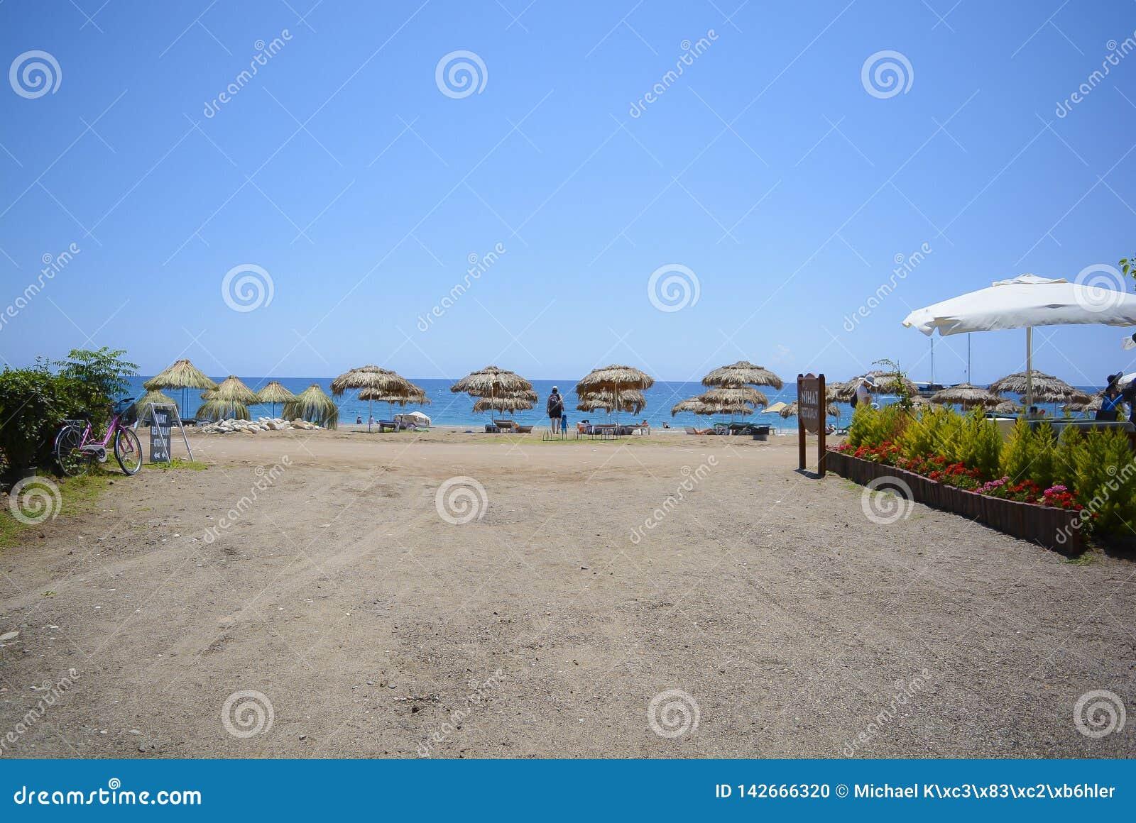 Playa, mar, paraguas de Sun, grava de las camas del sol