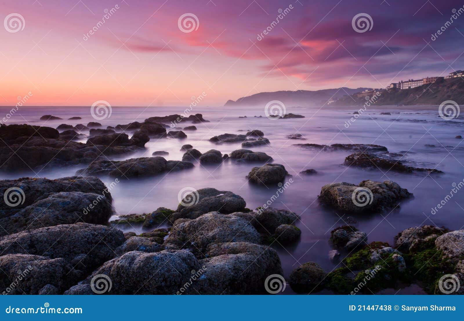 Playa soñadora lisa en la puesta del sol