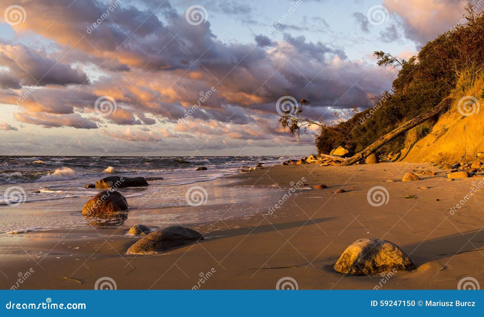 Playa y acantilado en el parque nacional de Wolin teniendo en cuenta la puesta del sol maravillosa