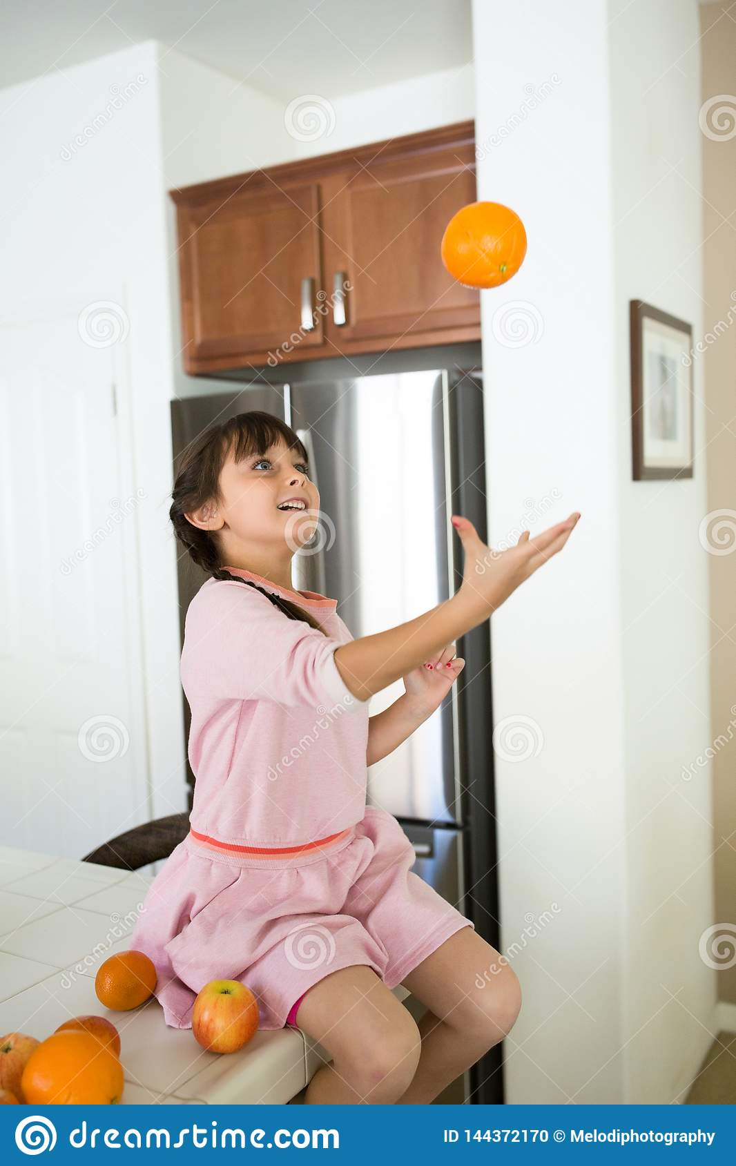 Girl in kitchen with oranges